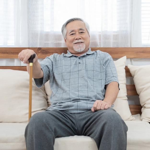 수석 노인 아시아 남자의 초상화 코치 손을 잡고 지팡이 지팡이 행복과 건강 한 라이프 스타일을 가진 집에서 소파에 앉아 도움이 앉아. 프리미엄 사진