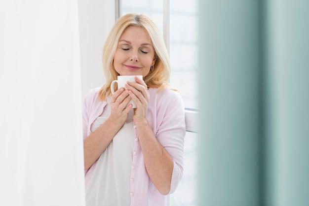一杯のコーヒーを楽しんでいる年配の女性の肖像画 無料写真