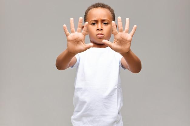 Портрет серьезного афроамериканского маленького мальчика, одетого в белую футболку, хмурящегося, с сварливым выражением лица, показывая все десять пальцев на обеих руках, не делая жестов или стоп Бесплатные Фотографии