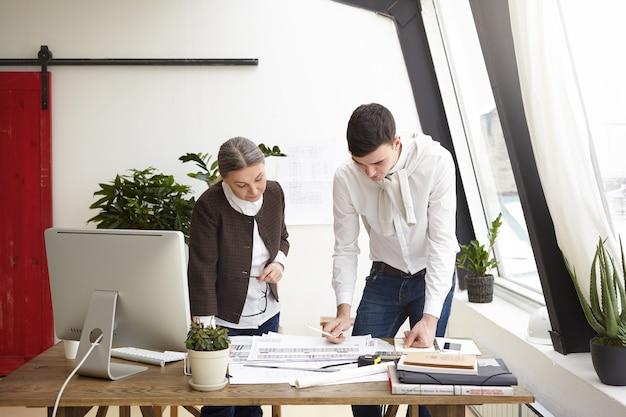심각한 창조적 인 전문 디자이너 젊은 남자와 프로젝트에서 작업 수석 여자의 초상화, 사무실 책상에 서, 주거 주택과 상업용 부동산의 인테리어 디자인을 만드는 무료 사진