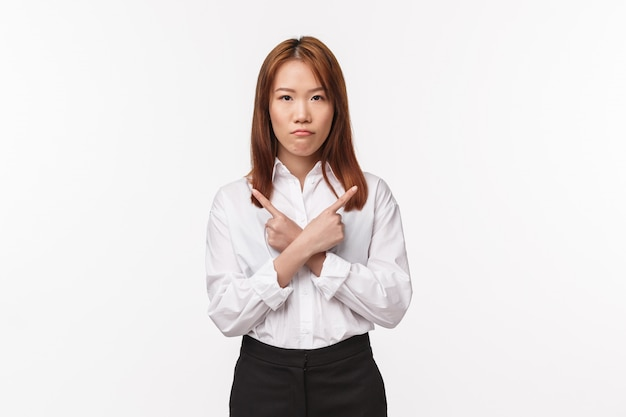 白いシャツで深刻に見える不機嫌な優柔不断なアジアの女性の肖像画、左と右を横切って横向き、失望と腹が立つ、白い壁 Premium写真