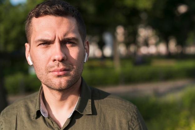Портрет серьезного человека, носить беспроводные наушники, глядя на камеру Бесплатные Фотографии