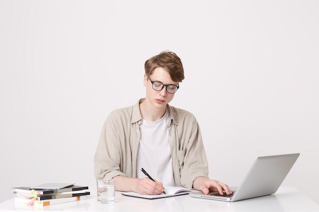 Портрет серьезного молодого человека-студента в бежевой рубашке и очках пишет и учится за столом, используя портативный компьютер и ноутбуки, изолированные на белой стене Бесплатные Фотографии