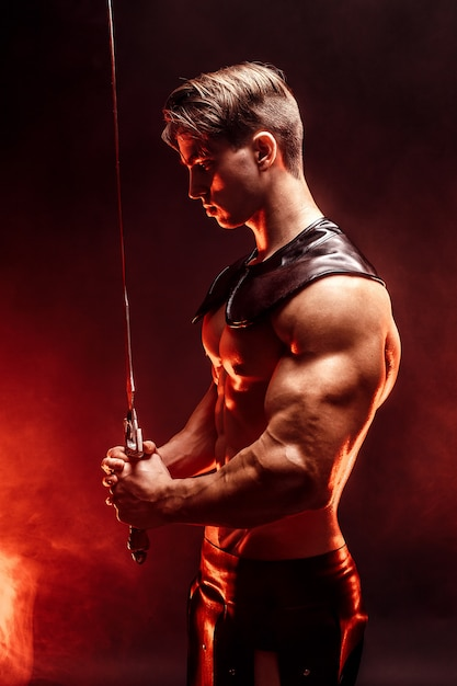 剣を保持しているセクシーな筋肉集中男の肖像画。 Premium写真