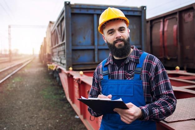 クリップボードを保持し、鉄道を介して貨物コンテナを発送する海運労働者の肖像画 無料写真