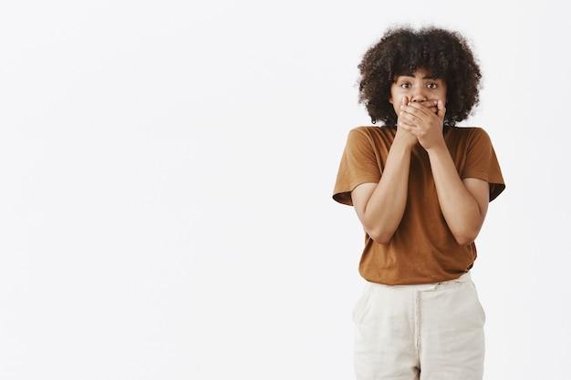 Портрет потрясенной безмолвной афроамериканки, ставшей свидетельницей шокирующей сцены, закрывающей рот обеими руками, стоя в ступоре и выглядела ошеломленной и потрясенной Бесплатные Фотографии