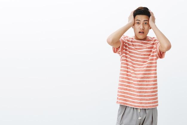 Портрет потрясенного молодого азиатского парня в ступоре, прижимающего руки к голове от изумления, безмолвного Бесплатные Фотографии