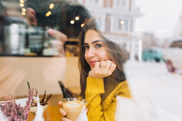Портрет застенчивой задумчивой женщины в связанном свитере, наслаждаясь кофе и смотря улицу. фотография в помещении романтичной молодой женщины в желтом наряде, мечтающей о чем-то во время обеда в кафе. Бесплатные Фотографии
