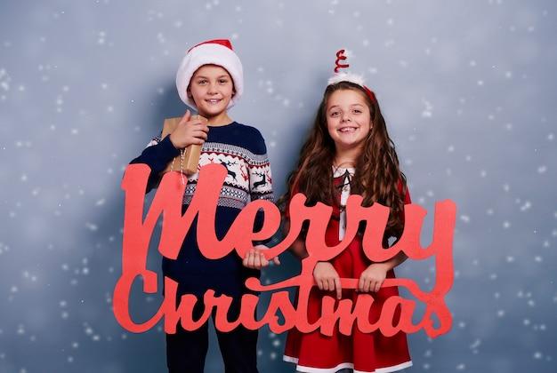 雪が降る中でクリスマス飾りと兄弟の肖像画 無料写真