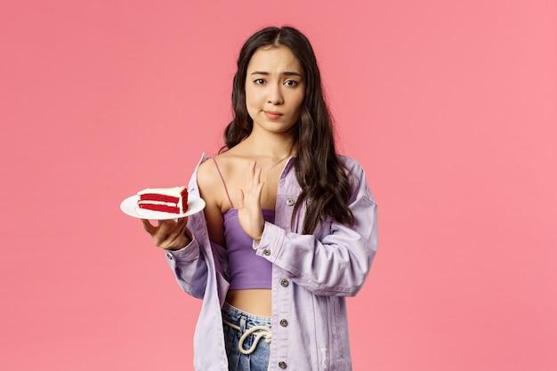 懐疑的な若いアジアのスタイリッシュなスリムな女の子がケーキを食べることを拒否する肖像画 Premium写真