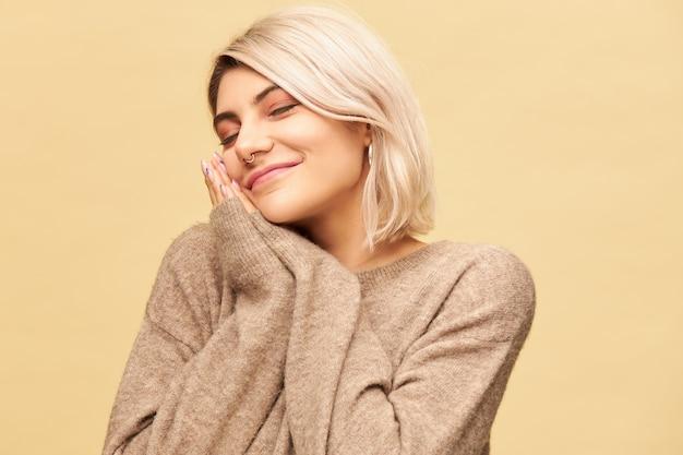 Портрет сонной усталой молодой блондинки с носовым кольцом, положив голову на прижатые друг к другу руки и с закрытыми глазами, дремлющей или спящей, счастливо улыбаясь. концепция сна, постельного белья и усталости Бесплатные Фотографии