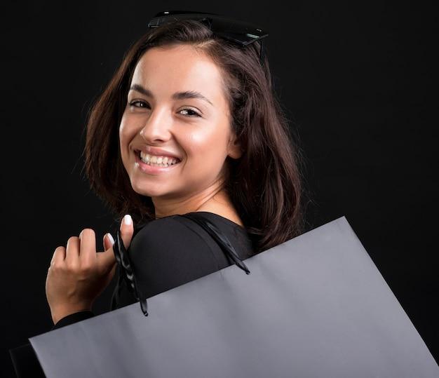 黒いバッグを持っている笑顔の女性の肖像画 Premium写真