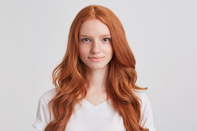 Портрет улыбающейся привлекательной рыжей молодой женщины с длинными волнистыми волосами Бесплатные Фотографии