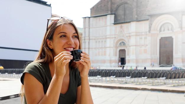 イタリアの屋外カフェに座って、コーヒーを飲みながら笑顔の美しい女性の肖像画 Premium写真
