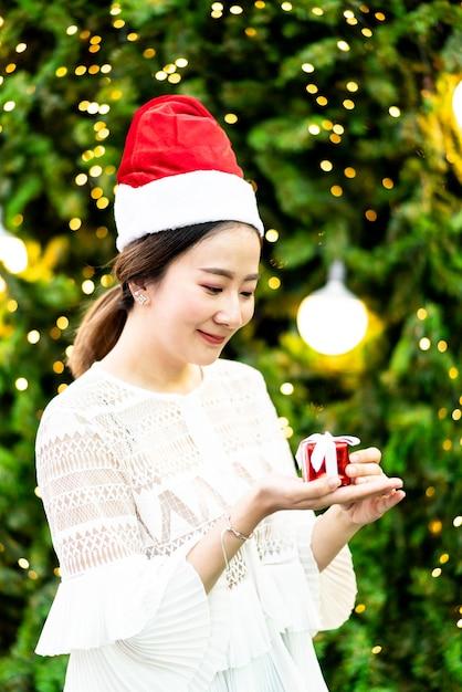 Портрет улыбающейся красивой молодой азиатской женщины с подарком на праздничной рождественской ярмарке Premium Фотографии