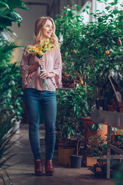 黄色の花を持って笑顔金髪の若い女性の肖像画 無料写真