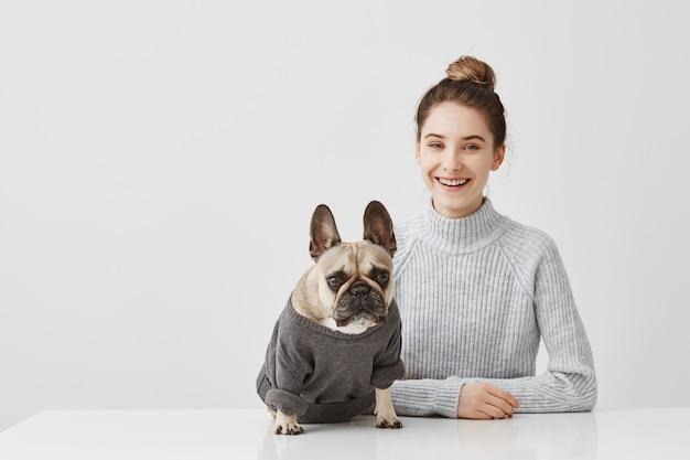 Портрет усмехаясь женщины брюнет при волосы связанные в topknot работая дома офис. женский фрилансер сидя за столом в мастерской в компании собаки. концепция дружбы Бесплатные Фотографии
