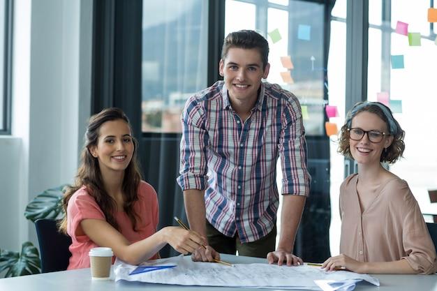 テーブルの上の青写真と経営幹部の笑顔のポートレート Premium写真