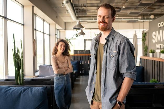 주머니에 손으로 서 현대 설립의 자신감 젊은 수염 소유자 미소의 초상화 프리미엄 사진