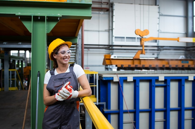 산업 생산 홀에 서 웃는 여성 공장 노동자의 초상화 무료 사진