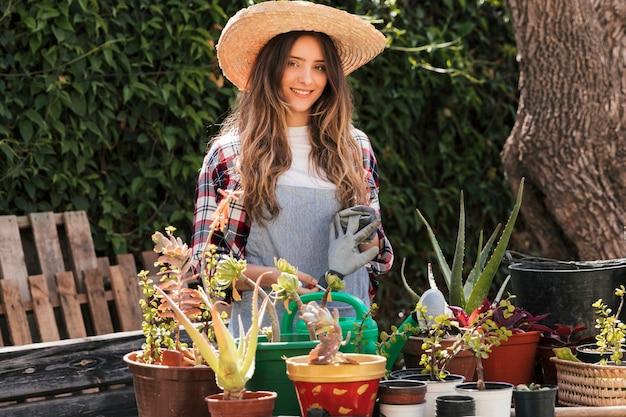 庭に立っている笑顔の女性庭師の肖像画 無料写真
