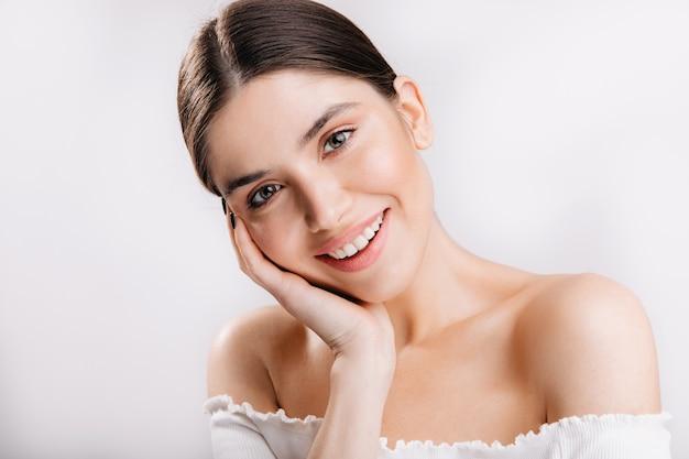 건강한 피부와 웃는 여자의 초상화입니다. 흰 벽에 귀여운 검은 머리 여자. 무료 사진