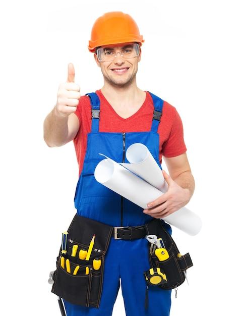 Портрет улыбающегося разнорабочего с инструментами и бумагой показывает палец вверх знак, изолированные на белом фоне Бесплатные Фотографии