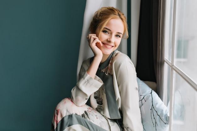 Портрет улыбающейся, счастливой блондинки рядом с окном, расслабляющейся утром, хорошо проводящей время дома. она одета в красивую шелковую пижаму. Бесплатные Фотографии
