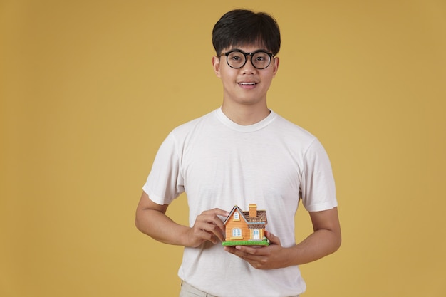 Портрет усмехаясь счастливого жизнерадостного молодого азиатского человека одетого небрежно при изолированная модель домашнего дома. концепция покупки недвижимости Premium Фотографии