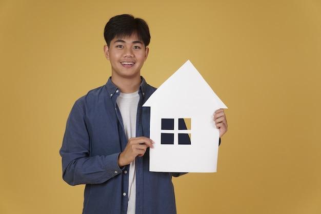 Портрет усмехаясь счастливого жизнерадостного молодого азиатского человека одетый случайно при изолированный вырез бумаги домашнего дома. концепция покупки недвижимости Premium Фотографии