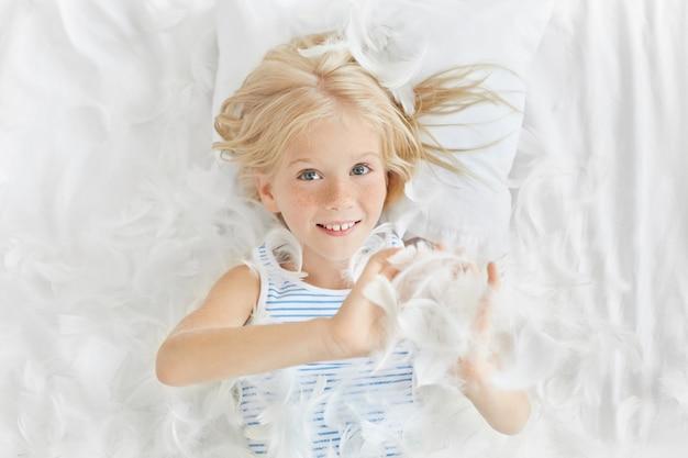 きれいな子供っぽい顔に遊び心のある陽気な表情を持っている公正な髪と白い羽で遊んでそばかすのあるベッドで横になっている笑顔のうれしそうな白人の赤ちゃん女の子の肖像画 無料写真