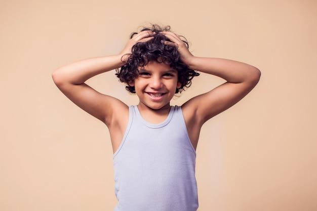 곱슬 머리를 가진 웃는 아이 소년의 초상화입니다. 어린이 감정 개념 프리미엄 사진