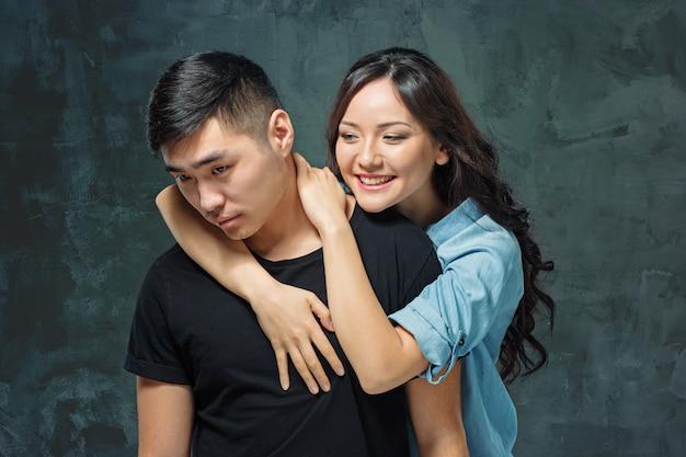 灰色のスタジオの背景に韓国のカップルを笑顔の肖像画 無料写真