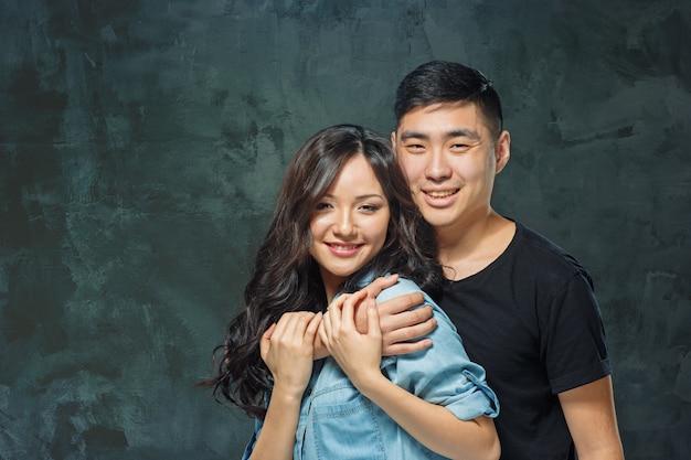 Портрет улыбающейся корейской пары на фоне серой студии Бесплатные Фотографии