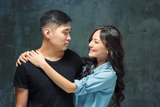 Портрет улыбающейся корейской пары в серой студии Бесплатные Фотографии