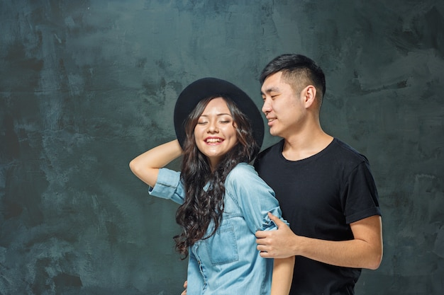 Портрет улыбающегося корейской пары на серой стене Бесплатные Фотографии