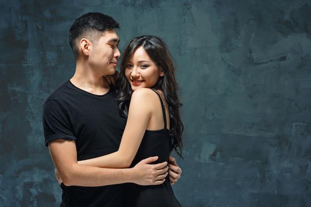 Портрет улыбающегося корейской пары на сером Бесплатные Фотографии