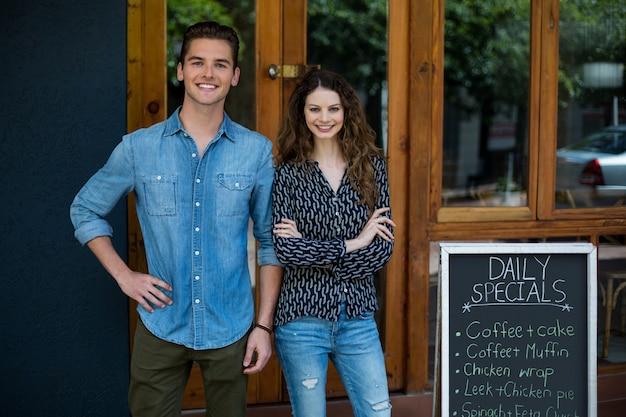 메뉴 보드 옆에 서있는 웃는 남자와 여자의 초상화 프리미엄 사진