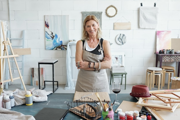 Портрет улыбающейся зрелой женщины в фартуке, стоящей со скрещенными руками в художественной студии с картинами на стене Premium Фотографии