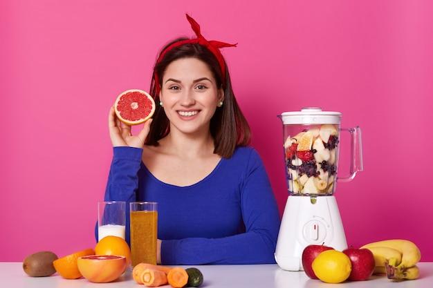 肯定的な女性の持株を笑顔の肖像画は彼女の手で果物をカットしました。若いモデルはスムージーの準備ができるのを待ちます。陽気な幸せな女は喜んで健康的な食事に固執します。健康的なライフスタイルのコンセプトです。 Premium写真