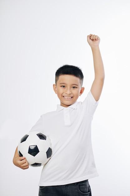 흰색에 고립 된 손에 축구 공을 점프 웃는 베트남 소년의 초상화 프리미엄 사진