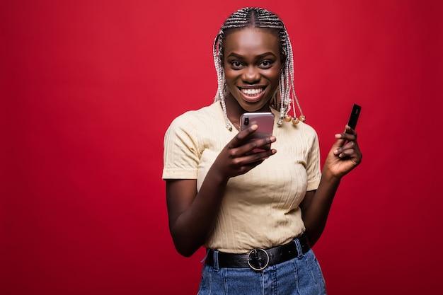 赤い背景の上に孤立した立っている笑顔の若いアフリカ女性の肖像画 Premium写真