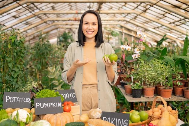 Портрет улыбающегося молодого азиатского садовника, который рекомендует есть яблоки при продаже органических продуктов на фермерском рынке Premium Фотографии