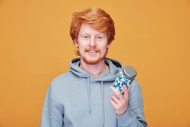 オレンジ色の健康のためにビタミンを服用しているパーカーの笑顔の若い赤毛の男の肖像画 Premium写真