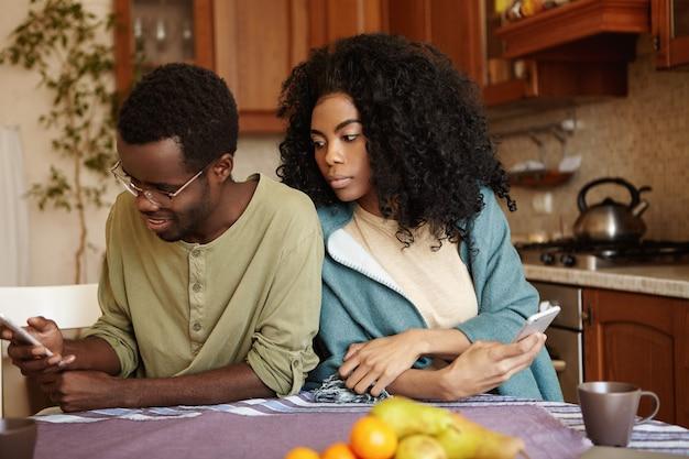 Портрет хитрой и ревнивой молодой африканской жены, шпионящей за своим мужем Бесплатные Фотографии