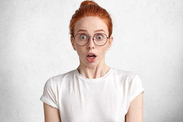 びっくりした生姜女子学生の肖像画は白いtシャツと大きな丸い眼鏡を着て、卒業証書を渡す期限があります 無料写真