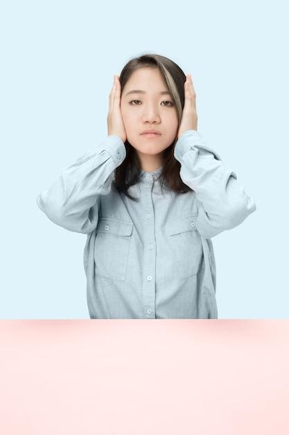 目を閉じて座って、手で覆ってストレスの多い女性の肖像画。青いスタジオの背景に分離。何も聞こえない 無料写真
