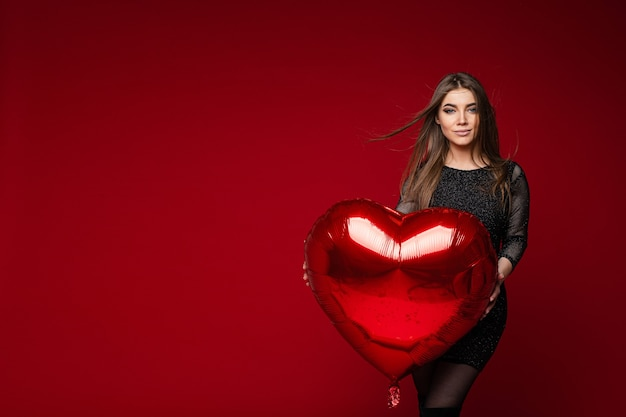 Портрет потрясающей девушки брюнетки в темном коктейльном платье с красным сердечным воздушным шаром на красном фоне. концепция дня святого валентина. Бесплатные Фотографии