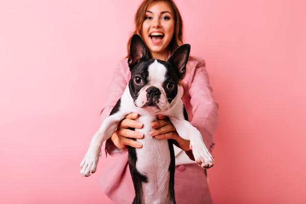 フォアグラウンドで小さな面白い犬とスタイリッシュなのんきな女の子の肖像画。フレンチブルドッグとの肖像画撮影中に良い感情を表現する黒髪の魅力的な白人女性。 無料写真