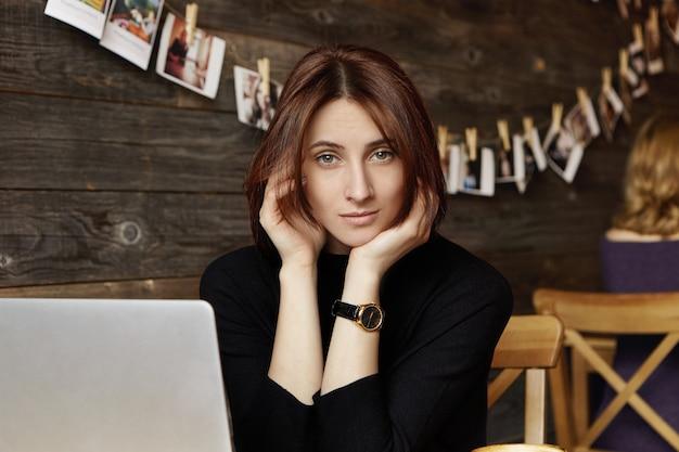 ノートパソコンの前に座っている腕時計を身に着けているスタイリッシュなかわいいブルネットの少女の肖像画、インターネットの閲覧、モダンなレストランでの無料のワイヤレス接続の使用、友人が彼女に昼食に参加するのを待っている 無料写真